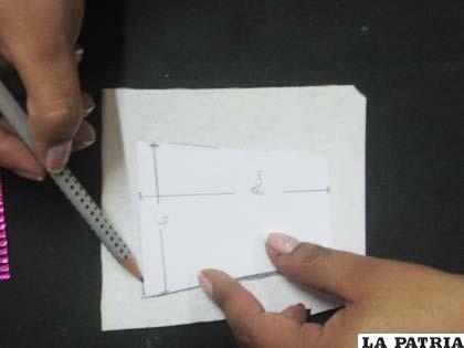 """PASO 1 Marcar con un lápiz la base del """"marcador de sitio"""", que tiene forma de vaso en el cartón ondulado corrugado blanco de 6 cm. por 8 cm."""