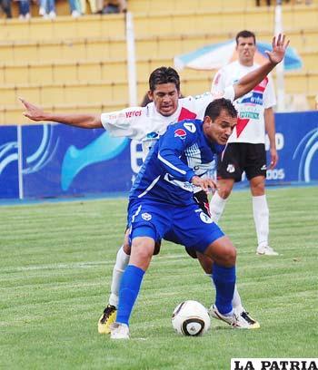 Santos Amador de Nacional, controla al goleador Bruno Juárez de San José. Lo anuló todo el partido.