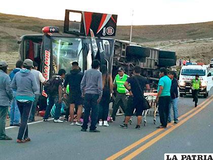 El bus sobre el asfalto mientras las demás personas intentan ayudar a los heridos
