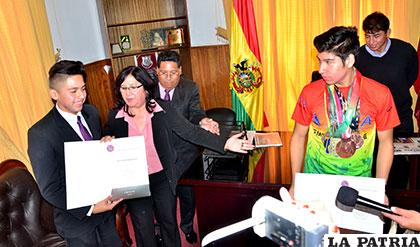 Gloria Romano hace la entrega del reconocimiento a Javier Olivares