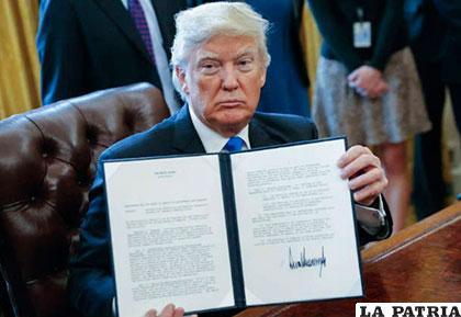 Presidente Donald Trump muestra su firma en una orden ejecutiva
