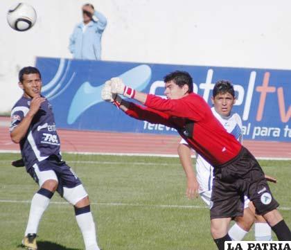 Carlos Lampe, despeja el balón ante la mirada de Alan Loras y Luis Palacios