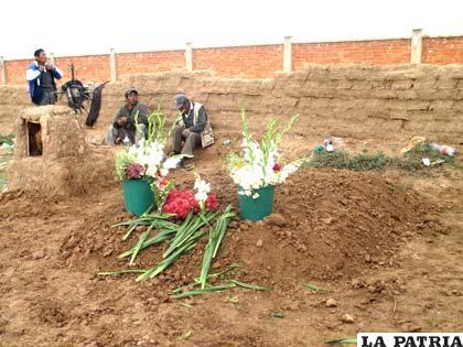 Pocas flores al pie de la tumba de la madre e hijas
