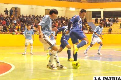 Saavedra, de Coobel, intenta dominar el balón ante la marca de su rival