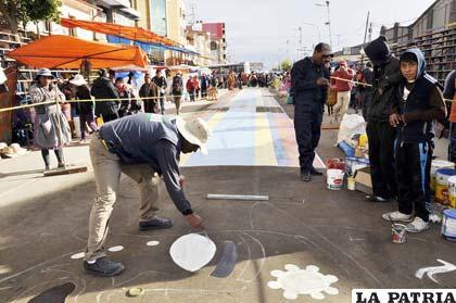 Artistas plásticos trabajando en medio de comerciantes
