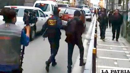 Momento en que el sindicado sale custodiado por un policía de la Felcv /ANF