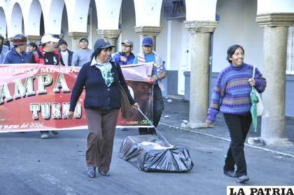 Mujeres arrastran un ataúd simulado que representó la Ley 045