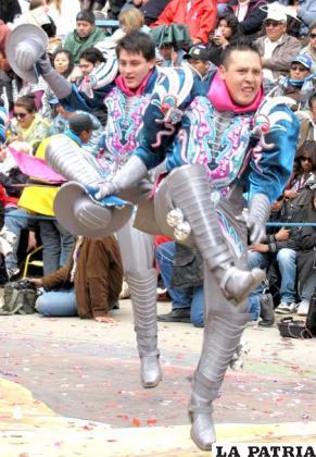MACHO CAPORAL: Este personaje es una proyección del actual caporal, en la danza forman grupos más pequeños a manera de figuras, los pasos y coreografía son más ágiles que los de la tropa. El macho caporal representa la fuerza y juventud de los varones, este grupo de danzarines fue creado en la década del 90 del siglo pasado. La blusa al igual a la de los otros personajes de los caporales, está hecha de lamé, con apliqués o bordados que se colocan tanto en el pecho como en la espalda, los puños están confeccionados con la misma tela del pantalón. Lleva un sombrero en la mano derecha, forrado con la tela del traje que lleva. El pantalón es ancho a la altura del muslo, sin adornos. La faja es ancha y hecha de cartón, muchas veces se coloca la inscripción del conjunto folklórico, bordado con lentejuelas. Las botas son de cuero y van hasta las rodillas, la punta es cuadrada, no lleva adornos, pero en los costados tiene filas de cascabeles.
