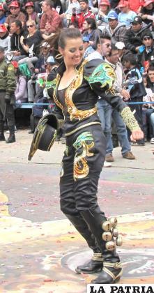 """MACHAS: Las """"machas"""" son personajes que fueron incluidos en la danza del caporal recientemente. Son mujeres que se visten de varón y representan la fuerza de las mujeres. En la danza forman grupos pequeños a manera de figuras,    creadas en la década del 90 del siglo pasado. Lleva el cabello largo y recogido hacia atrás. Utiliza una blusa con mangas anchas y altas sin cuello. En la parte del pecho como de la espalda lleva apliqués que por lo general son alusiones a la mitología del Carnaval de Oruro, como víboras, lagartos u hormigas. Los puños ajustados y las mangas anchas, están decorados con lentejuelas. Algunas llevan en la mano izquierda un látigo de cuero trenzado, que es símbolo de autoridad, a diferencia de los varones que llevan el látigo en la mano derecha. El pantalón es de terciopelo, a veces es ancho a la altura de los muslos, que es una característica del traje del caporal. Lleva una serie de bordados o apliqués con lentejuelas en alto relieve en las piernas. La faja está hecha de cartón forrado con tela y decorada con lentejuelas. Las botas son de cuero hasta las rodillas, con punta cuadrada, forradas y adornadas, cuyo complemento principal es la fila de cascabeles a los costados de las botas."""