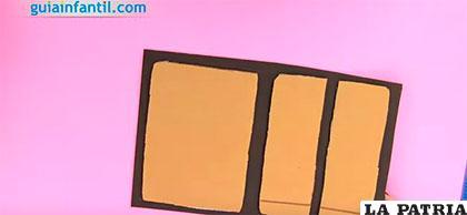 PASO 2 Pon uno de los cartones enteros y el recortado a la mitad sobre una plantilla de goma eva negra. Antes de pegarlos deja 1,5 centímetros por arriba, abajo y los laterales. Entre los dos cartones deja 2 centímetros de espacio.