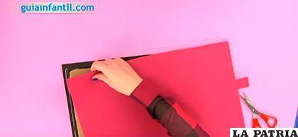 PASO 3 Recorta un rectángulo de goma eva roja, del mismo tamaño que la negra y pégalo sobre ella. Recuerda dejar un piquito que será el cierre.