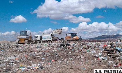 El trabajo de compactado de basura con maquinaria en el relleno sanitario /EMAO