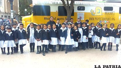 Los niños de la U.E. Juana Azurduy de Padilla junto al bus del proyecto Meraki /LA PATRIA