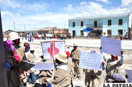 En primer plano comunarios que marcharon, de fondo la Alcaldía tapiada y los seguidores del alcalde de Chipaya