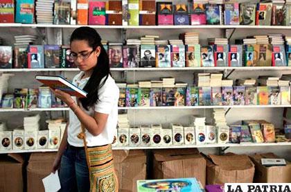 Una estudiante observa un libro en la Feria del Libro dominicana