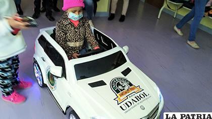 Una pequeña paciente de Oncohematologia en uno de los vehículos donados/ANF