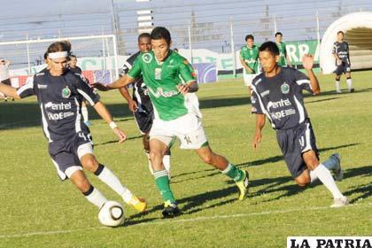 Alcides Peña, intenta penetrar entre dos defensores