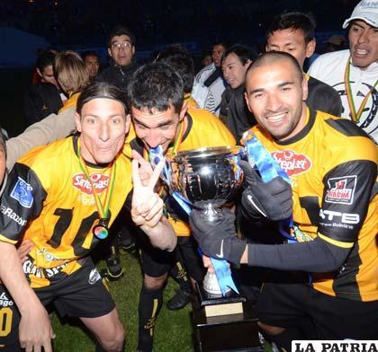 Escobar, Ojeda y Cristaldo con el trofeo de campeón