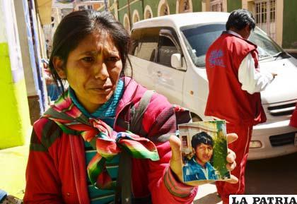 La tía muestra la foto del muchacho perdido