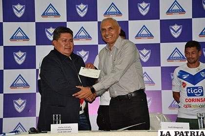 Carlos Estrada recibe el cheque de manos de Vasili Kitaigorod