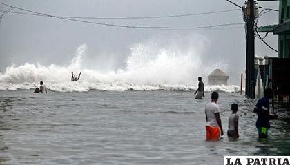Pese al intenso oleaje, varias personas caminan dentro del agua en una zona del Malecón habanero en La Habana, Cuba /EFE