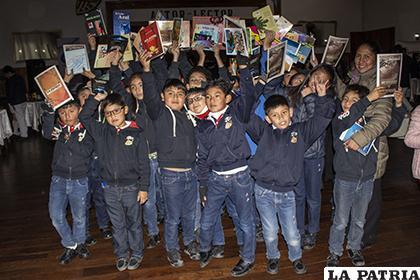 Niños contentos por llevarse sus libros después de visitar la feria /LA PATRIA/Alejandro Valdez