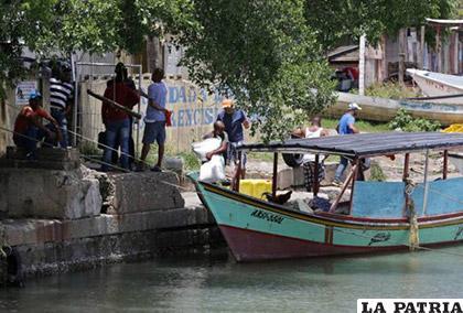 Venezolanos cargan un barco de comida y bienes comunes para llevar de regreso a su país, en el puerto de San Fernando, Trinidad /Reuters