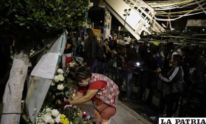 Una mujer coloca flores en un altar improvisado durante una protesta en demanda de justicia para las personas que fallecieron /AP Foto/Eduardo Verdugo