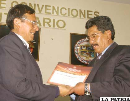 El director Departamental de Educación, entregando el diploma de reconocimiento a uno de los 203 maestros meritorios