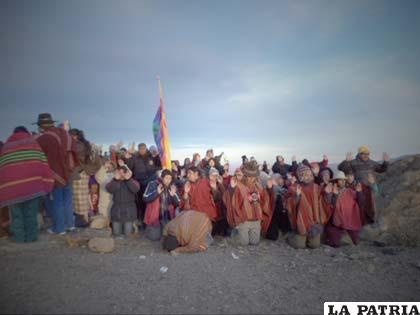 Comunidad arrodillada frente a la aurora