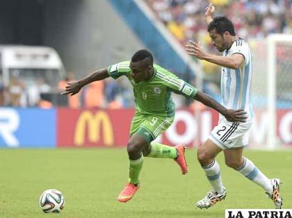 Emenike de Nigeria domina el balón ante la marca de Garay