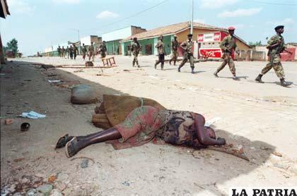 Soldados de la resistencia pasan junto al cadáver de una mujer