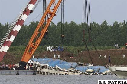 Una grúa reflota el barco naufragado en el río Yangtsé (China)