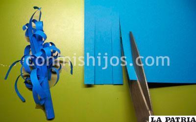 PASO 4 Ahora recorta una tira ancha en la cartulina azul, y tiras más finitas a lo largo de ésta, pero sin llegar a separarlas. Luego dale forma a cada tira enrollándola con la técnica de