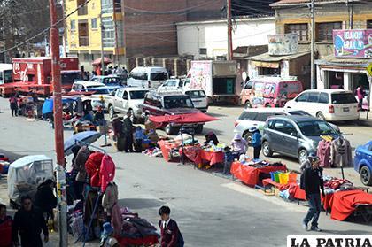Una fila de vehículos pasando sobre los rieles por la obstrucción generada por los comerciantes