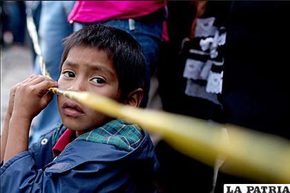 Un niño observa cerca al lugar donde permanece el cuerpo de un hombre que fue asesinado con un arma de fuego en una calle, en Ciudad de Guatemala