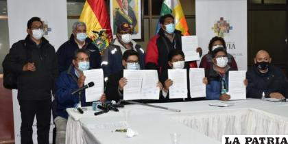 Trabajadores muestran el acuerdo suscrito por autoridades de Gobierno  /MINISTERIO DE OBRAS PÚBLICAS