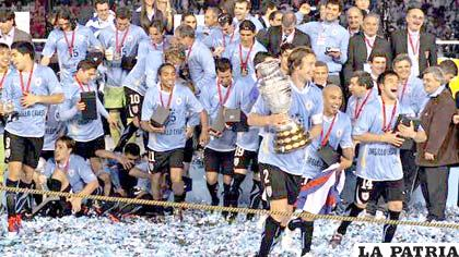 Diego Lugano, capitán de la selección de Uruguay con el trofeo de campeón