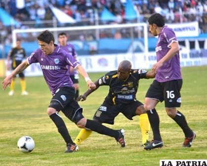 Nelson Cabrera escapa con el balón ante la marca de un atigrado mientras Walter Flores observa