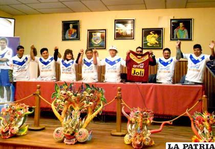 Dirigentes de ambas instituciones al final de la conferencia se pusieron la camiseta del equipo