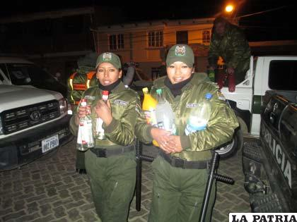 Dos uniformadas llevan las bebidas decomisadas por estar vencidas