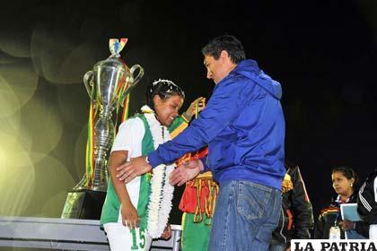 Tito Montaño hace la entrega del trofeo a la capitana de Santa Cruz