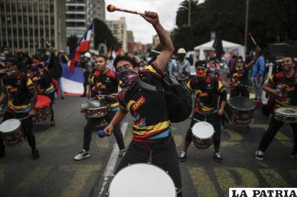 Jóvenes tocan tambores durante una protesta en contra del gobierno (AP Foto/Ivan Valencia)