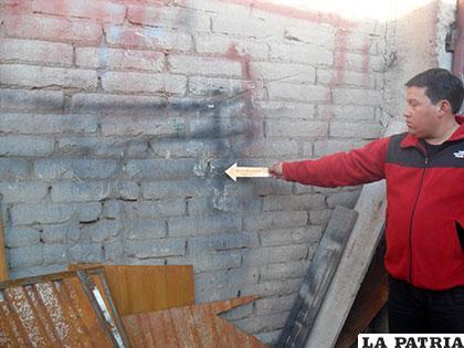 Un investigador muestra el muro por donde ingresaron los vándalos