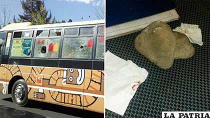 Los vidrios rotos del vehículo de transporte público. Al lado una de las piedras /ALCALDÍA LA PAZ