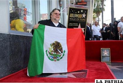 El cineasta posando con la bandera de México y su estrella en el Paseo de la Fama /AP