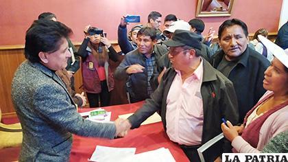 El alcalde, Saúl Aguilar y el dirigente gremial, Marcelino Arancibia se dan la mano tras la firma de acuerdo /LA PATRIA