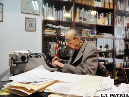 Luis Ramiro Beltrán entre papeles y su máquina de escribir