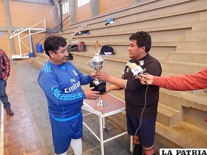 Ramos entrega el trofeo de campeón a Fernández, del equipo de Sedes