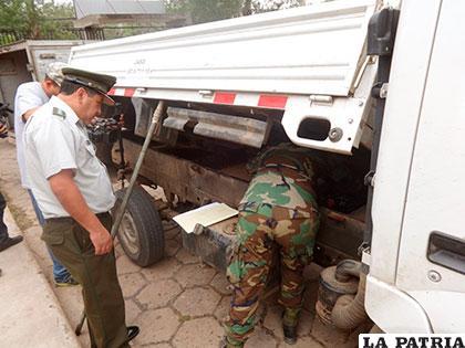 Personal policial antidroga revisa el doble fondo en la carrocería del vehículo